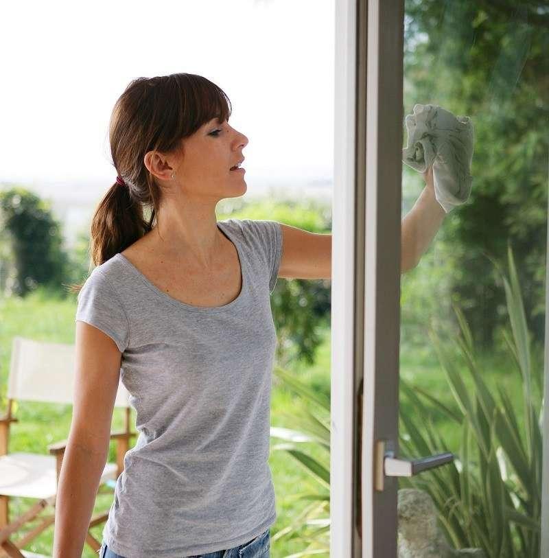 Femme à l'extérieur nettoyant les vitres d'une maison